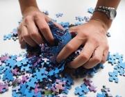 Mans agafant peces de puzle