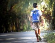 Nen d'esquena amb motxilla caminant