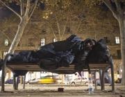 Una persona sense sostre dorm en un banc al costat de la Ciutadella