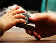 Una mà adulta li dóna una càmera de fotos a una mà infantil