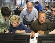 Voluntaris ensenyant a fer servir l'ordinador a gent gran. Font: ara.cat
