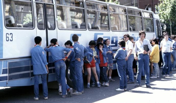 Joves escoltes esperant per pujar a l'autocar per marxar de campaments