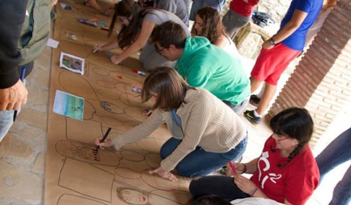 Grup de joves pintant un mural, en una activitat de l'SCI-Cat