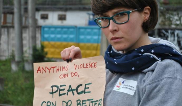 Aga Stajer amb un cartell que diu en anglès: Qualsevol cosa que pugui fer la violència, la pau la pot fer millor Font: Youth Peace Ambassadors Network (Facebook)