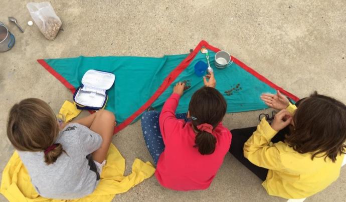 Tres nenes menjant amb carmanyola. Font: Minyons Escoltes i Guies de Catalunya