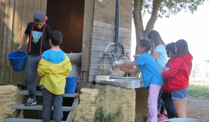 Un grup d'infants rentant plats i omplint cantimplores durant els campaments. Font: Minyons Escoltes i Guies de Catalunya