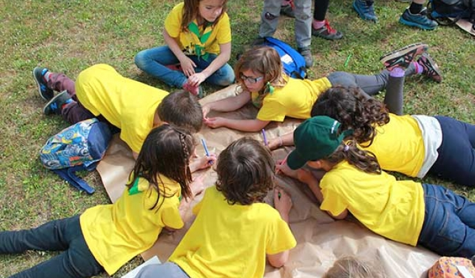 Un grup d'infants fent una activitat damunt la gespa
