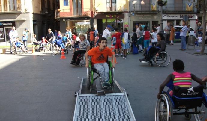 Acció de sensibilització on joves fan slaloms amb cadires de rodes.