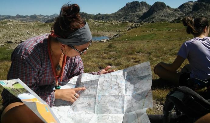 Una noia escolta mirant un mapa a l'Estany de Sant Maurici