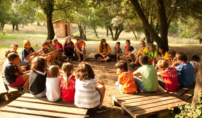 Un grup d'infants asseguts en rotllana damunt d'uns palés. Font: Minyons Escoltes i Guies de Catalunya