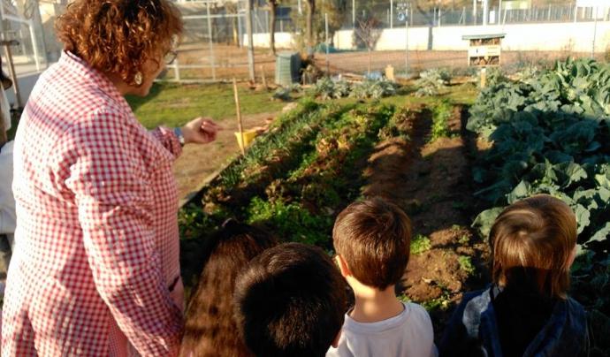 Mestra i alumnes a l'hort de l'Escola Mediterrània