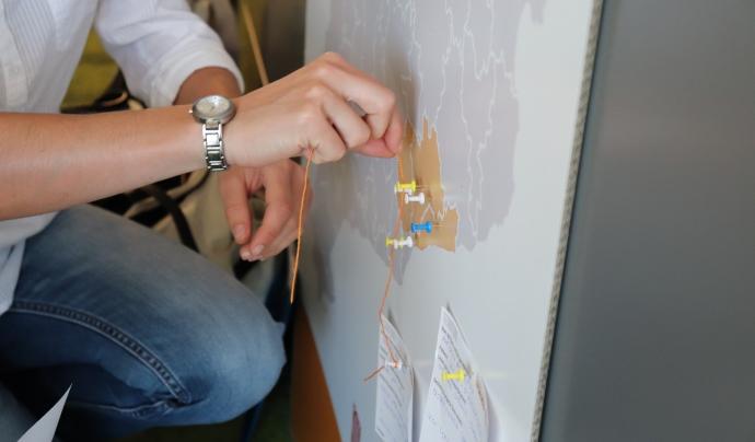 Trobada territorial dins de la JdIS. La imatge mostra unes mans enganxant una fitxa en un mapa
