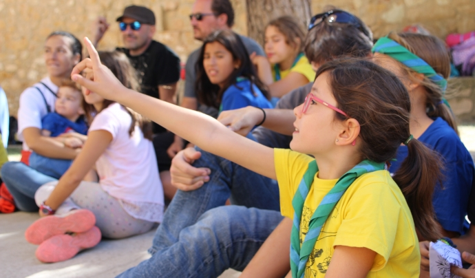 Una nena participants en una activitat amb la mà alcaça per dir la seva.