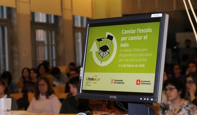 Un ordinador que mostra la diapositiva de presentació de la II Trobada 'Canviar l'escola per canviar el món'