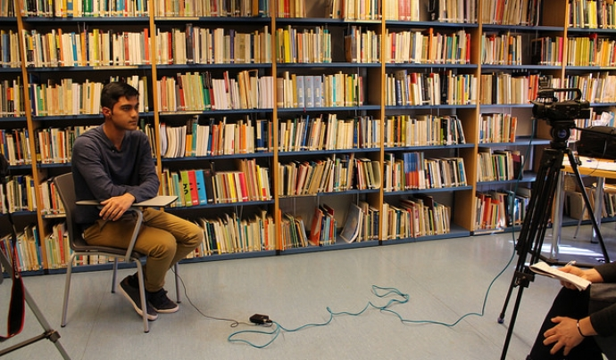 Un jove explicant les seves reflexions davant de la càmara, en una biblioteca.