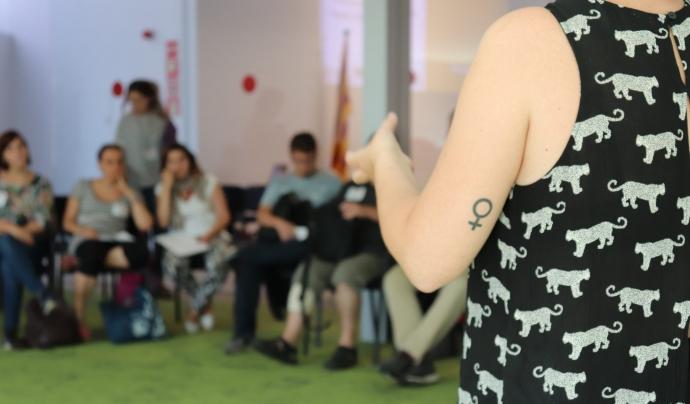 Núria Alonso presentant el taller sobre perspectiva de gènere a la JdIS. En la foto es veuen persones de fons i un braç amb el símbol de les dones tatuat
