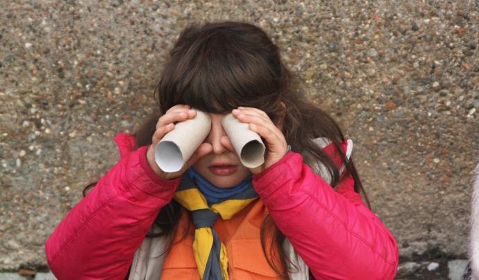 Una nena utilitzant els rotlles de paper higiènic com a prismàtics. Font: Minyons Escoltes i Guies de Catalunya
