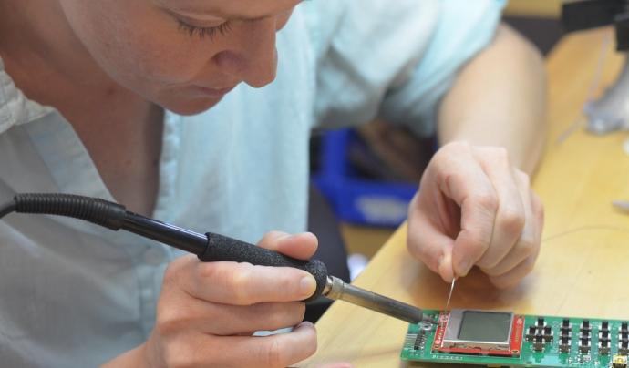 """Dena doing repairs on her phone"" de dam (CC BY 2.0)  Font: Dam (CC BY 2.0)"