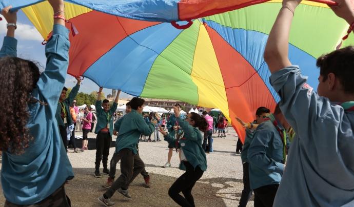 Infants jugant amb un paracaigudes de colors