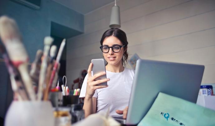 Una noia treballant amb ordinador i telèfon mòbil. Llicència CC0: https://www.pexels.com/photo-license/ Font: Bruce Mars (Pixels)
