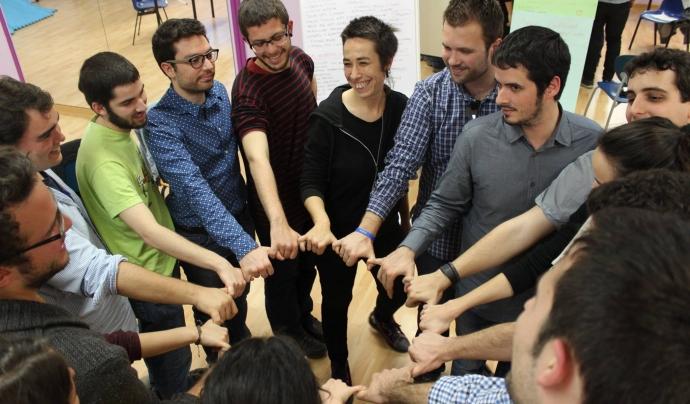 Joves en una rotllana posant les mans al centre en una activitat de la 10a Àgora Jove, posant