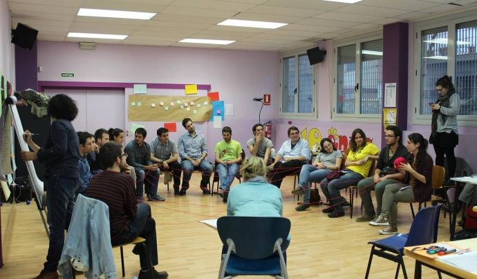 """Un grup de joves """"teixint xarxes"""" passant-se simbòlicament un cordill els uns als altres en una activitat de la 10a Àgora Jove."""