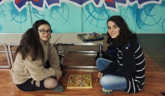 Un dels 'tàndems' format per una noia universitària i una jove, jugant a un joc de taula.