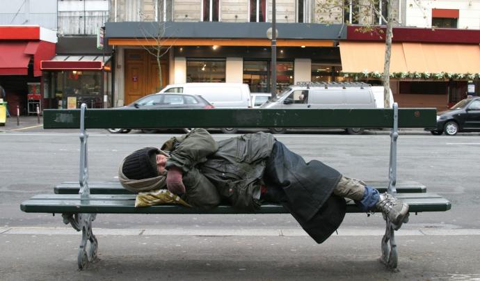 Una persona dorm en un banc