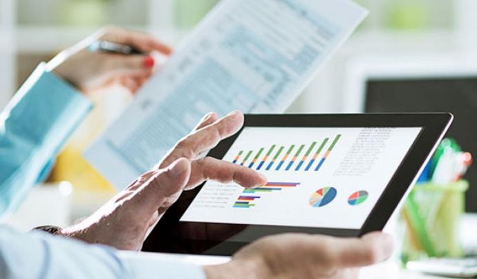 Persona treballant amb una tablet en què hi apareixen gràfics