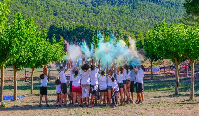 Un grup d'infants jugant amb pols de colors