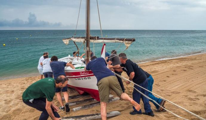 Portar a l'aigua una embarcació a la manera tradicional requereix moltes persones Font: A tot drap