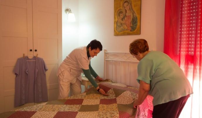 Una auxiliar atén a una persona gran a casa seva. Font: ECAS