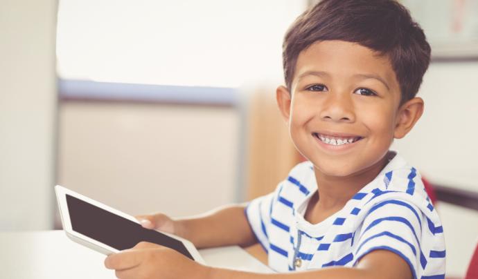 Un nen agafa una tablet a casa per poder continuar amb la seva rutina escolar. Font: Fundació IRES
