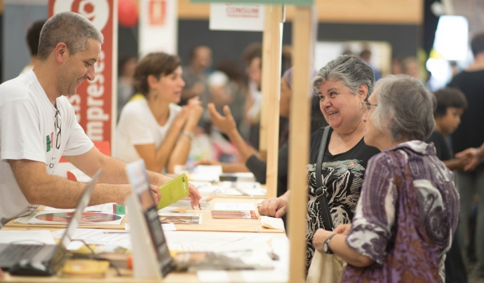 Dues dones demanen informació a un estand de la FESC. Font: FESC