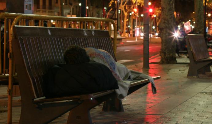 Persona sense llar dorm al carrer enmig de la nit.  Font: Voluntaris.cat