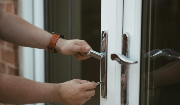 Una persona atesa obre la porta de casa seva per rebre el menjar. Font: PxHere