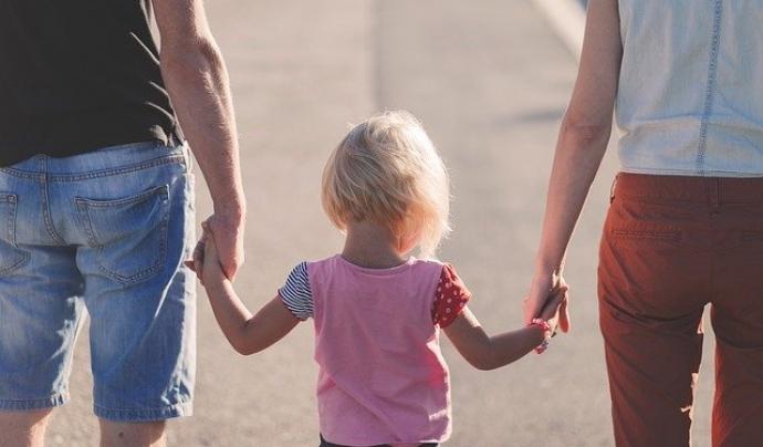 Una família camina, agafant de la mà a la seva filla. Font: Pixabay