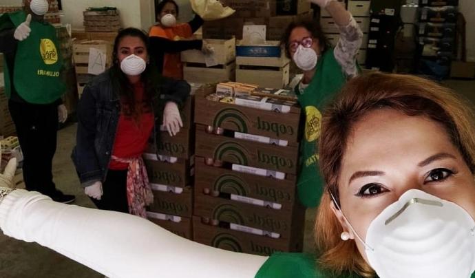 El voluntariat de l'ONG Gra de Blat prepara els aliments que seran repartits a domicili. Font: Gra de Blat