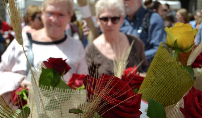 Dues dones que passegen per les Rambles s'aturen per mirar una rosa. Font: FCVS