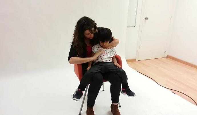 Alba Florejachs durant la sessió fotogràfica juga amb l'Olenka, un dels infants amb pluridiscapacitat. Font: Youtube
