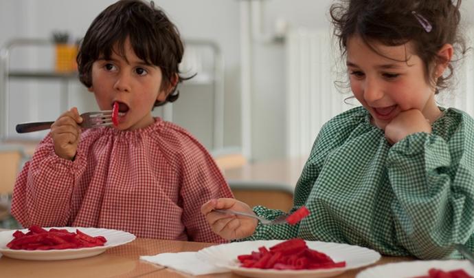 Infants menjant macarrons amb salsa de remolatxa - Menjadors escolars ecològics Font: Associació menjadors ecològics (Facebook)