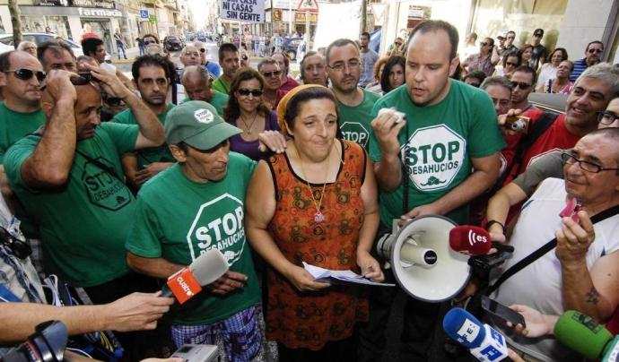 Una afectada per un desnonament rep el suport popular perquè no la facin fora del seu pis. Font: Anticapitalistes