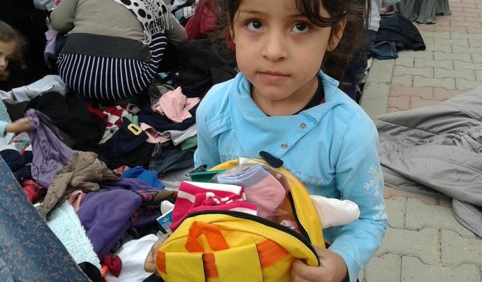 Una nena siriana mira a la càmera amb la mirada perduda, sostenint una motxilla. Font: Pixabay