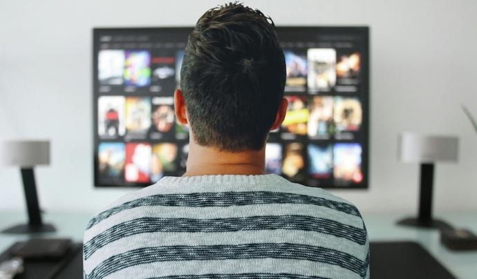 Un jove selecciona una sèrie a la plataforma Netflix.  Font: Public Domain Pictures