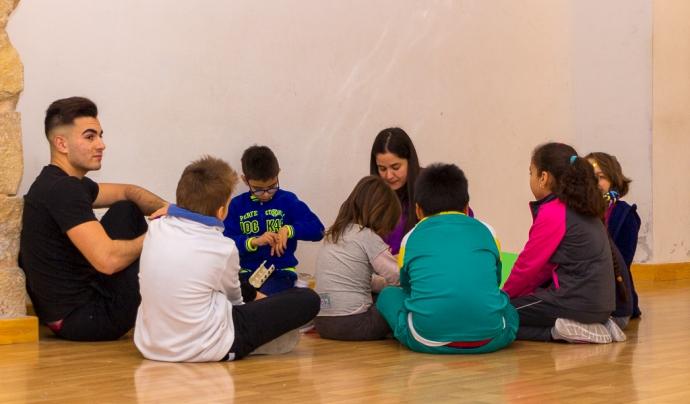 Monitors de lleure amb grup d'infants asseguts al terra