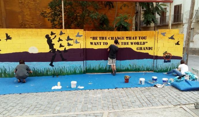 Paret pintada en blau i groc amb un lema solidari