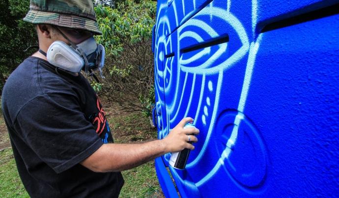 Jove de la Comuna 13 pintant un autobús. Font: Facebook