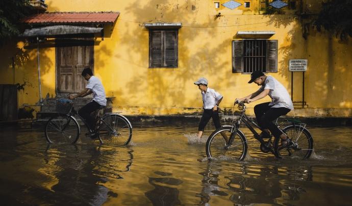 Nens en bicicleta en un carrer inundat per les pluges. Font: Llicència CC