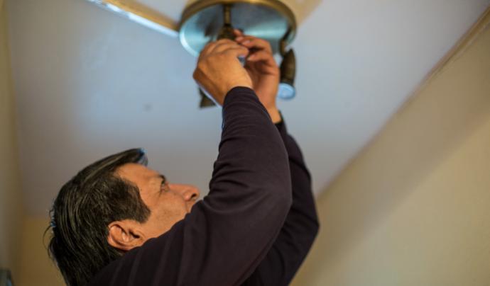 Un home canviant una bombeta de casa