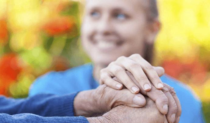 Imatge de les mans d'una persona gran agafades per una cuidadora